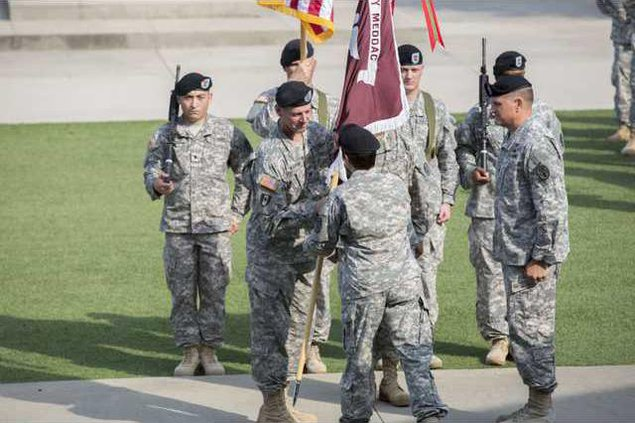 Col Ahearne takes the guidon from Brig Gen Barbara Holcomb during change of command ceremony