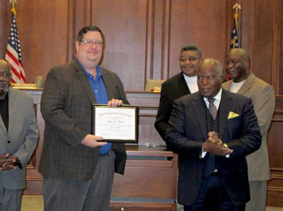 Hinesville City Council member Jason Floyd receives a certificate of recognition for completing the Harold F Holtz Muncipal Training for Elected Officials before Thursdays city council meeting