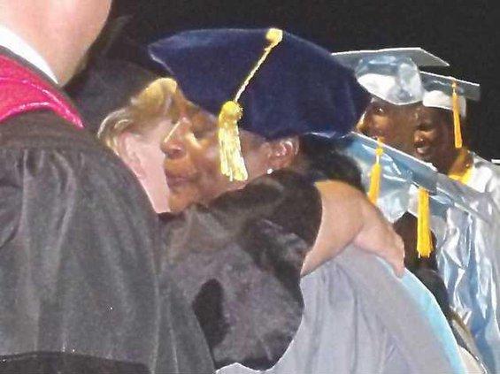 Dr. Mallard hugs a fellow teacher
