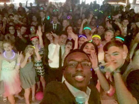 Keinan Johnson takes a selfie with a large group of Bradwell students at the Midnigt in Paris-themed homecoming danceweb