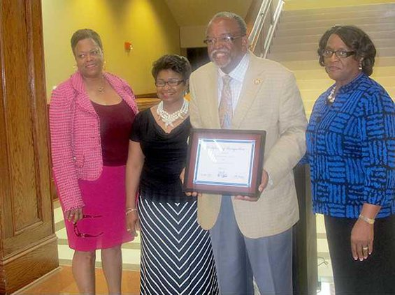 Representative Al Williams holds his recognition certificate for being named Legislator of the Year. left to right Dr. Valya Lee Olivia Williams wife Board Chairwoman Lily Baker