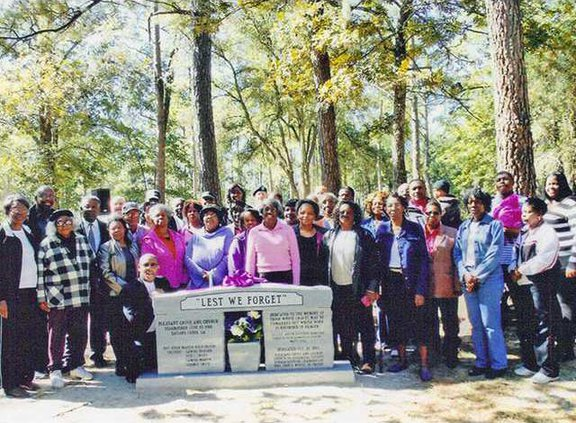 Former residents and church members pose with new marker