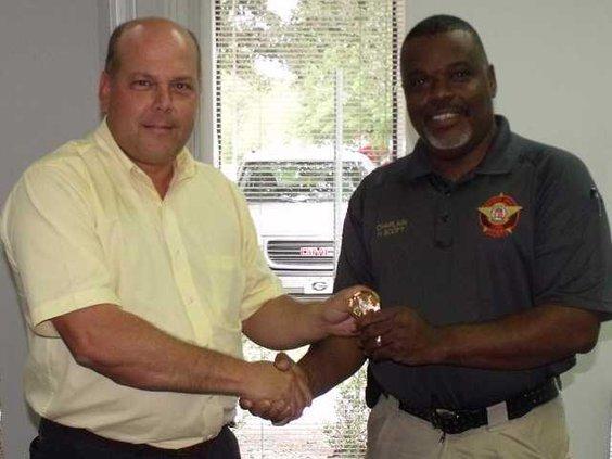 Sheriff Nobles presents badge to Chaplain Herman Scott