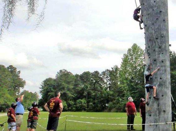 2 Boy Scouts scaling rock wall