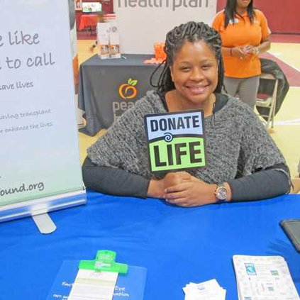 Amanda Hollowell holds up a sign encouraging people to become organ donors