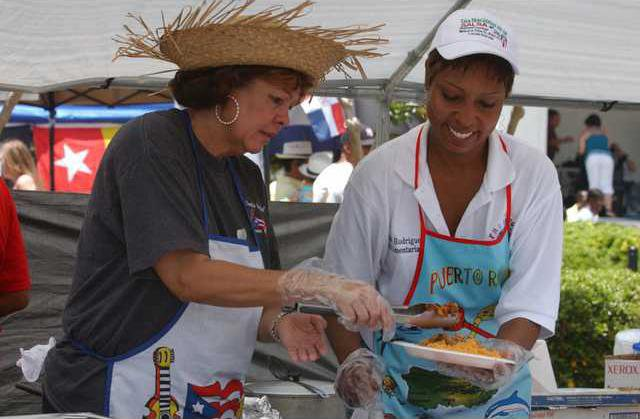 Maria Rodriguez and the Fort Stewart Hispanic Heritage Club serve food