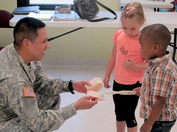 CDC kids show Sgt. Galarza how to properly brush teeth