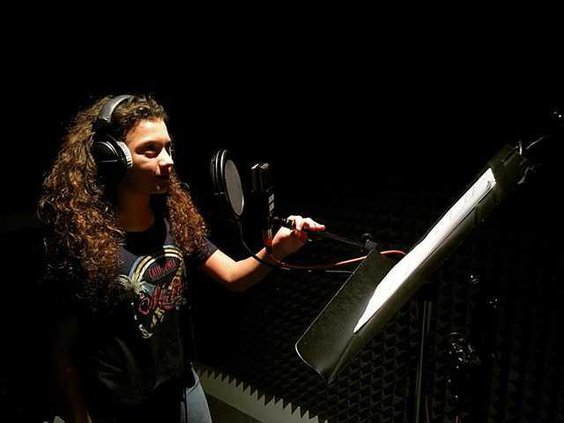 Merrik working in the sound booth doing a voice over. Photo provided
