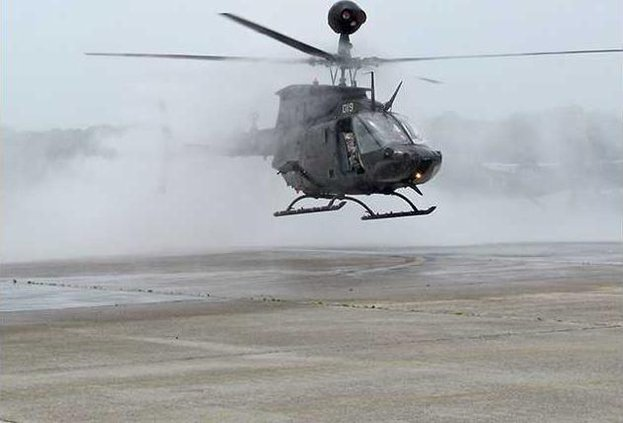 a Kiowa emerges from water cannon spray as part of final flight ceremony