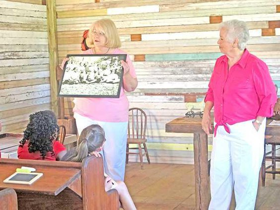 Julie Martin left and Barbara Martin right show a picture of students who attended the one-room school house