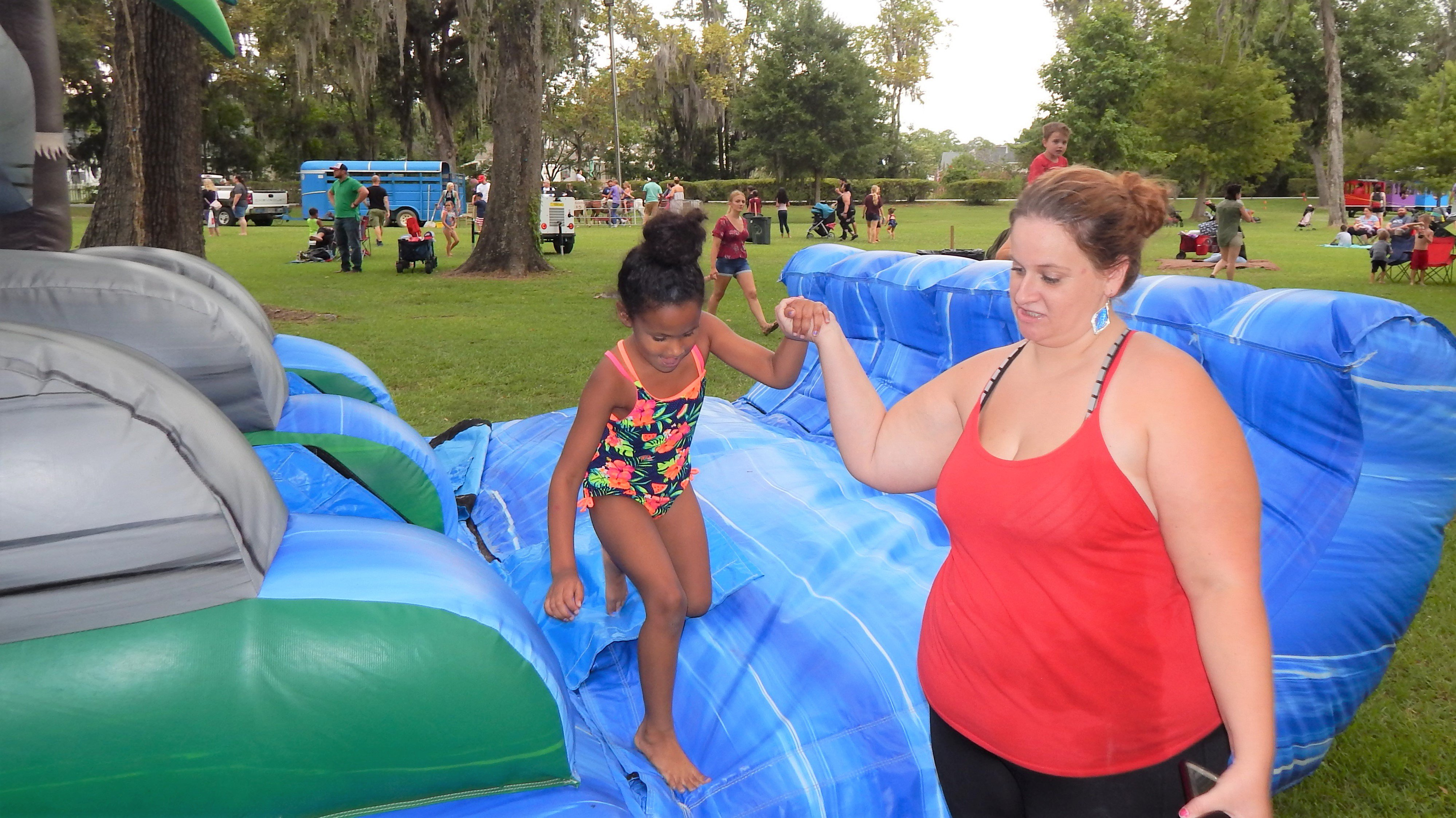 A young girl gets assistance out of the water slide. Photo by Mark Swendra