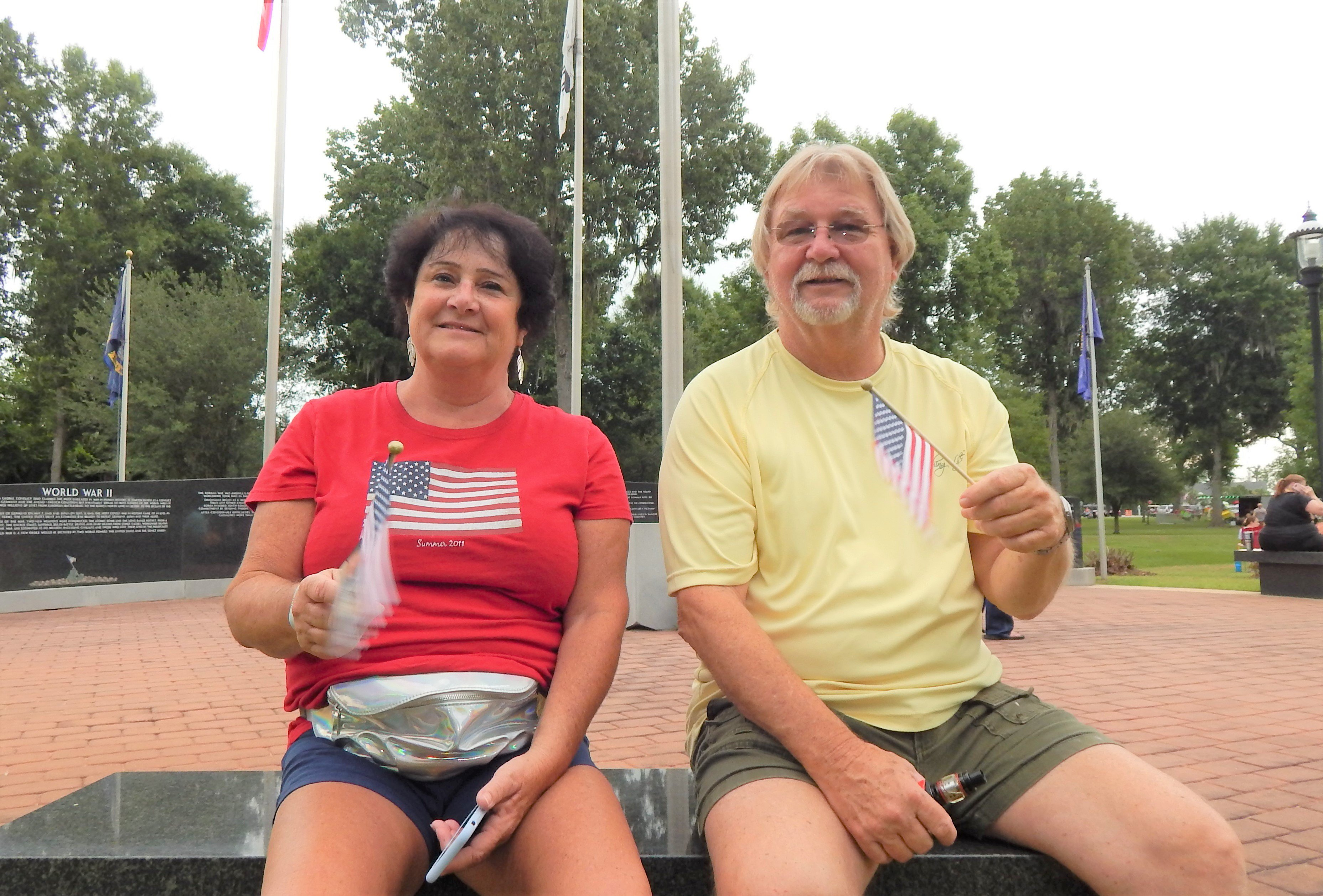 This couple waved their flags as they sat at the war memorial. Photo by Mark Swendra